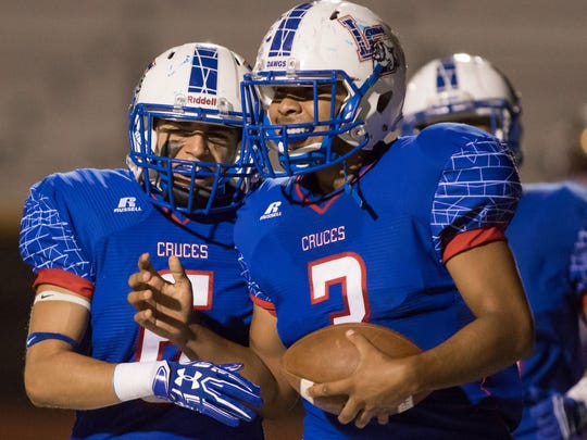 Las Cruces High's Gabe Quezada is all smiles after he picks up a blocked kick and runs it in for a touchdown during Thursday night's football game against Gadsden High School the Field of Dreams.