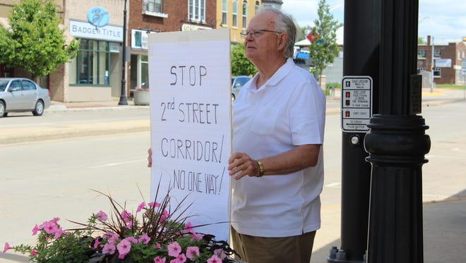 Carl Scott holds a sign in downtown Marshfield in June 2015 protesting a proposal to convert a part of Second Street to one-way traffic.