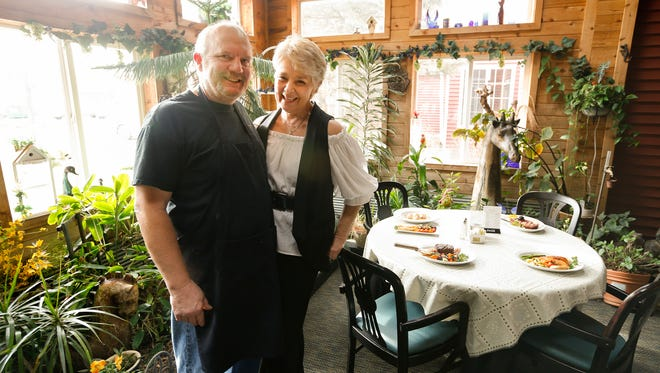 Jeff and Terri Jensen, owners of the Fieldstone Inn in rural Stanhope, stand in the garden room, a dining room with a year-round garden and water feature.