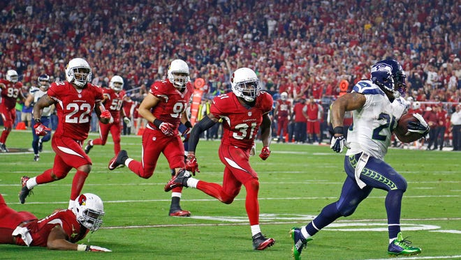 Seattle Seahawks running back Marshawn Lynch (24) runs away from the Arizona Cardinals defense to score a touchdown in the 4th quarter quarter of their NFL game on Dec. 21,  2014 in Glendale.