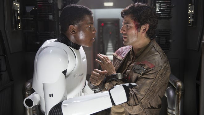 """New bros Finn (John Boyega) and Poe Dameron (Oscar Isaac) plan their escape from a Star Destroyer in """"Star Wars: The Force Awakens."""""""