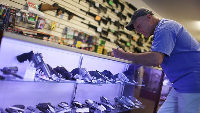 Mark O'Connor fills out his federal background check paperwork in Delray Beach, Fla., as he purchases a handgun Tuesday, the day that President Barack Obama announced steps to strengthen the background check system for firearms purchases..