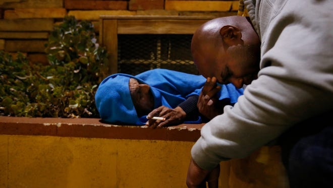 Anthony Ruffin, 48, right, kneels to speak with a homeless man sleeping in the bushes on Jan. 30, 2017 in Hollywood, Calif.