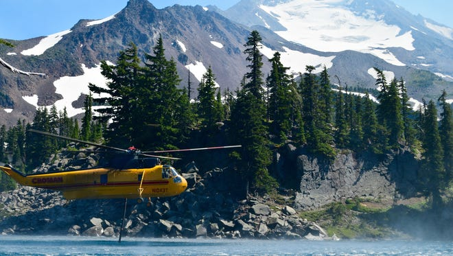 Helicopters lift water Aug. 6, 2017, from a lake in Jefferson Park, Ore., along the Pacific Crest Trail in the Mount Jefferson Wilderness to fight the Whitewater Fire. The basin was closed to hikers a day later.