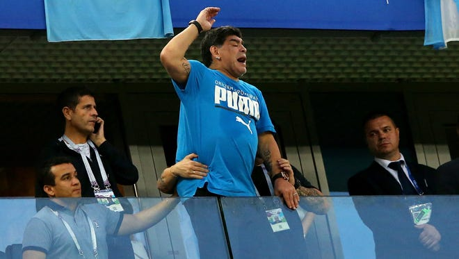 Diego Maradona shows his support from the stands at Saint Petersburg Stadium.