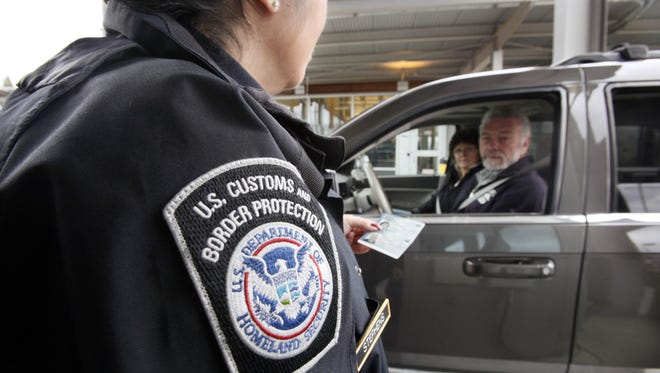 U.S. Customs and Border Protection officer Victoria Stephens speaks with a couple using NEXUS identification cards at a border crossing from Canada into the United States at Blaine, Washington.