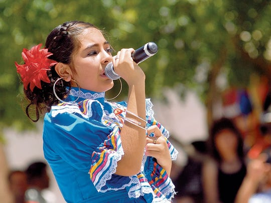 Gisell Mata sings as East Picacho Ballet Folklorico dancers perform at the 2014 Cinco de Mayo Fiesta on the Mesilla Plaza.