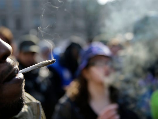 People smoke marijuana cigarettes as a large group gathered near the New Jersey Statehouse to show their support for legalizing marijuana Saturday in Trenton. The event drew a diverse crowd of roughly 200 people.