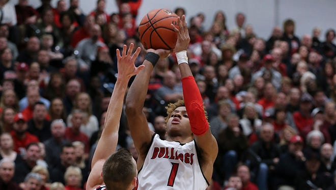 New Albany's Romeo Langford (1) hits a jumper with Bedford North Lawrence's Gaven Moore (14) putting a hand in his face during their game at New Albany High School.  It is Langford's last home game.