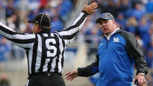 Kentucky's Mark Stoops questions the official during the first half against Georgia.
