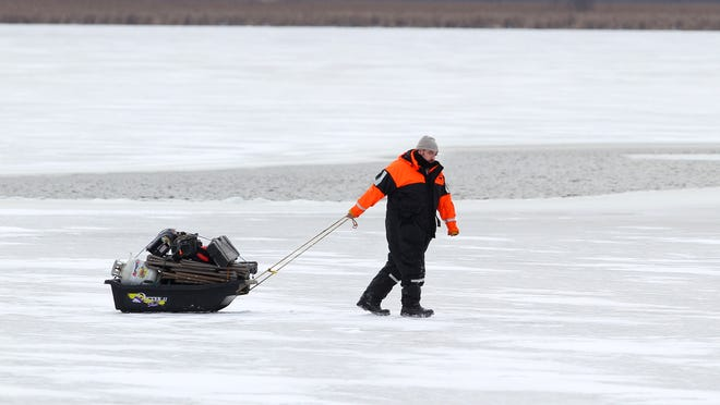 Jeff McCulloch pulls his sled of fishing gear a safe distance past open water on Cranberry Pond in Greece. McCulloch and his friends traveled from Buffalo to find to ice fish and spent more than four hours on the water catching three fish. The group agreed it was worth the trip.