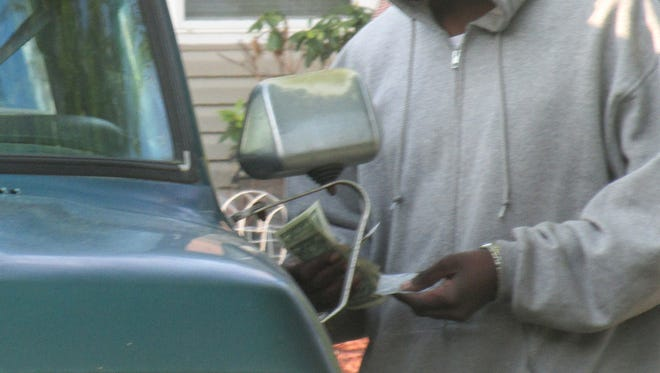 An exchange of money for a small package takes place in this photo, recently shot in Deaverview Apartments. Police and the Housing Authority say they are addressing the open air drug market problem.