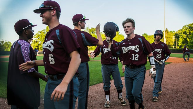 Collierville's Mitch Austin (12) is congratulated by teammates after scoring a run against Harding.