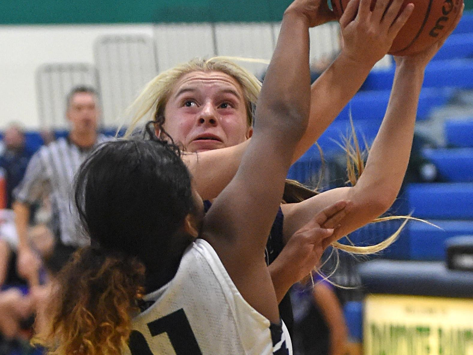 Damonte's Alexus Hunter blocks a shot by McQueen's Kendra McAninch early in Tuesday's game at Damonte Ranch High School.