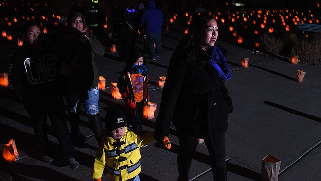 Leann Charlie, right, her son, Codie Charlie, 3, left, and the rest of her family enjoy the luminaria display on Saturday at San Juan College.