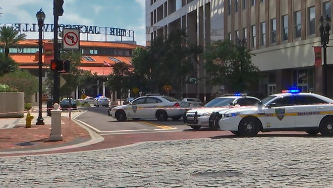 Police cars block a street leading to the Jacksonville Landing area in downtown Jacksonville on Aug. 26, 2018, in this image from TV station WJXT.