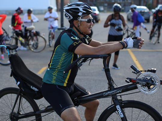 Wayne State University President M. Roy Wilson listens to the ride organizer while sitting on his recumbent bike before they ride out to train for Wayne State University's Baroudeur, a cycling event to raise money for scholarships, in Detroit on Wednesday, Aug. 12, 2015.