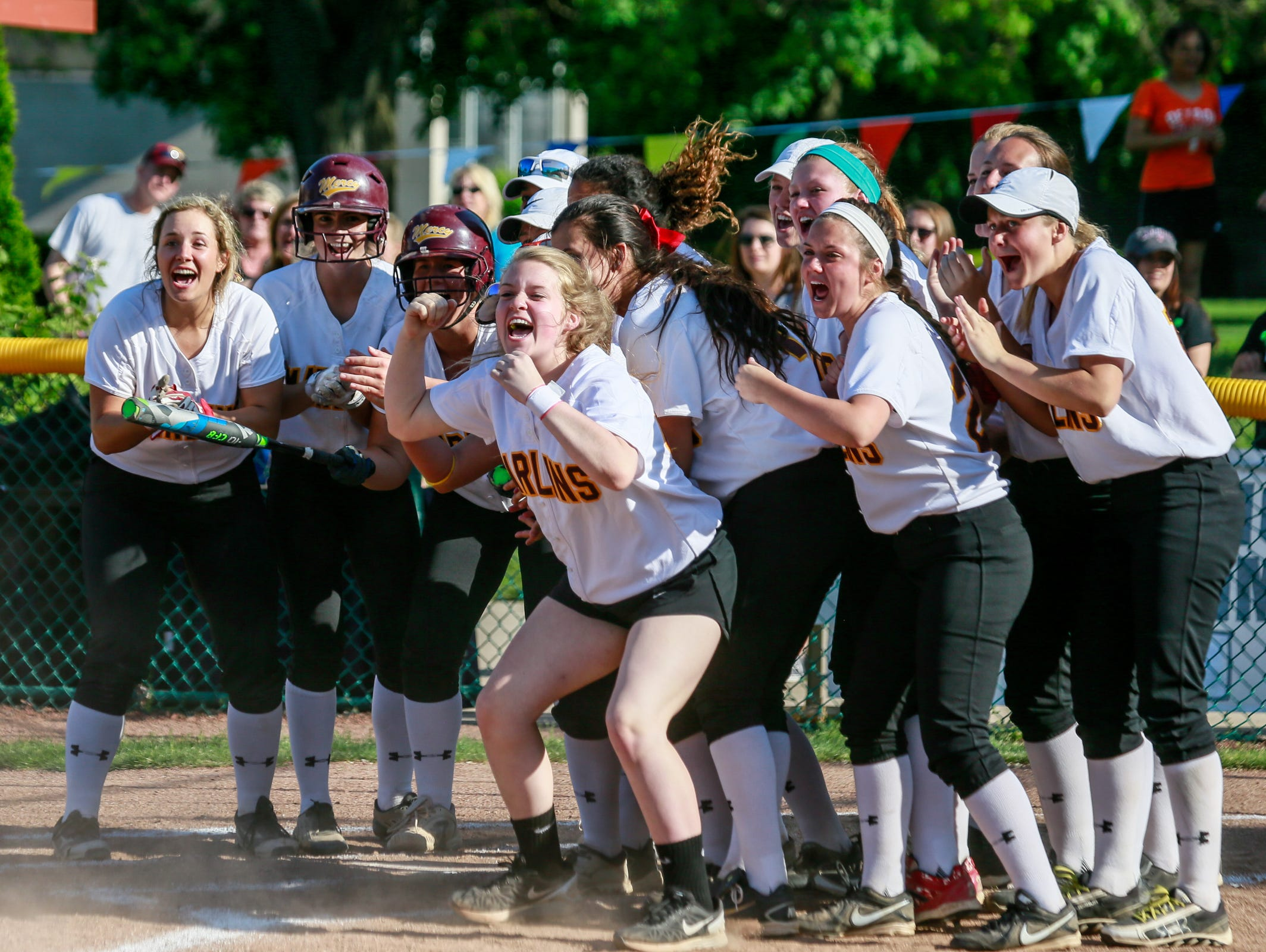 Farmington Hills Mercy players wait for Anna Dixon at home plate after she hit a home run against Pontiac Notre Dame Prep during the A-B Division Catholic League softball championship in Detroit on May 23, 2016.