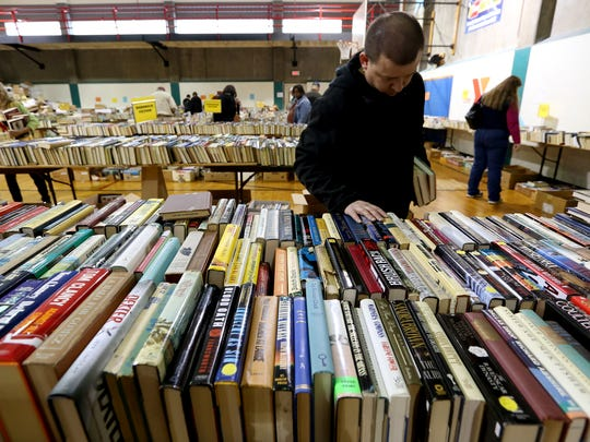 Jimmy Kemper, 34, of Salem, looks through fiction titles during the 63rd annual YMCA Used Book Sale in Salem on Saturday, March 4, 2017. The sale continues Sunday with readers able to buy all they books they can fit into a bag for $3 and a box for $5.