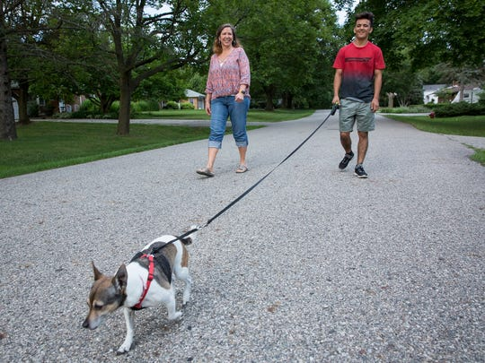 Yuu, 18, right, and his foster mother Judi Harris of Okemos, walk their dog Tilly in the neighborhood, Friday, July 14, 2017 in Okemos.