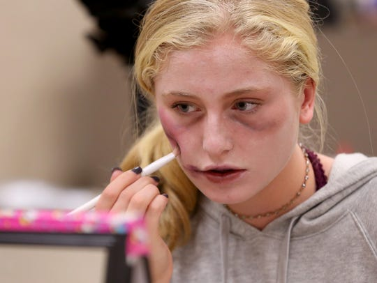 Aria Dyson, 16, of Salem, draws a bruise on her cheek