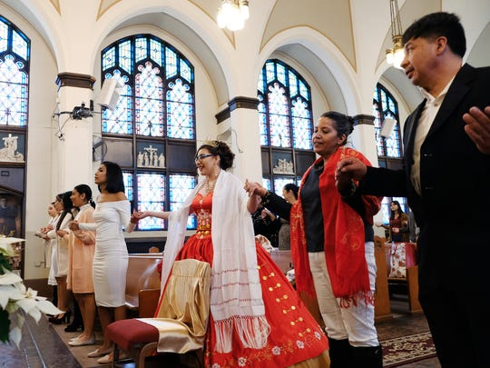 Fatima Flores of Detroit holds hands in prayer with family and friends during her quinceanera ceremony in the sanctuary of All Saints Church in Detroit on Friday, Dec. 29, 2017.
