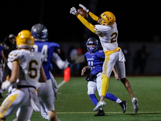 Rochester Adams' Vincent Gray (2) tries to intercept