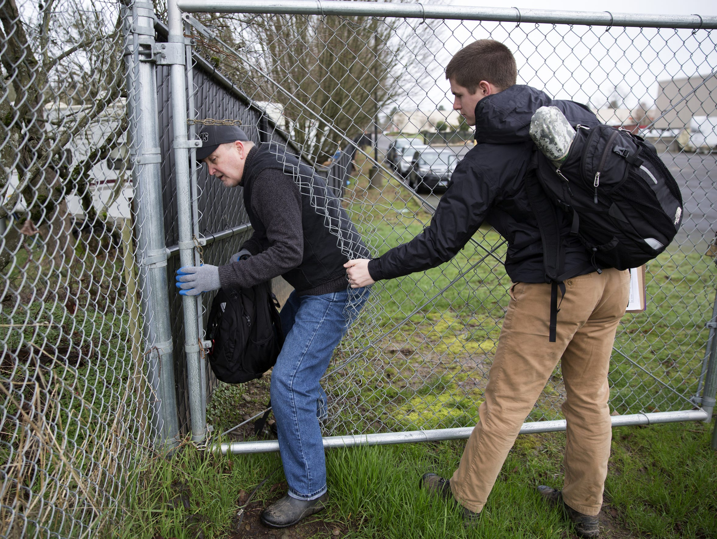 Volunteers Jerry Stevens, left, and Bryce Petersen slip through a hole in a fence to try and find a homeless camp during the Homeless Point-in-Time count near Highway 22 in Salem on Wednesday, Jan. 31, 2018.