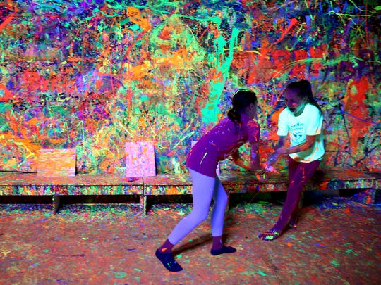 Lily Bennett, 11, left, and Averil Shonk, 12, both of Albany, have a paint fight inside the Splatter Box at the Albany Art Studio on Wednesday, March 28, 2018.