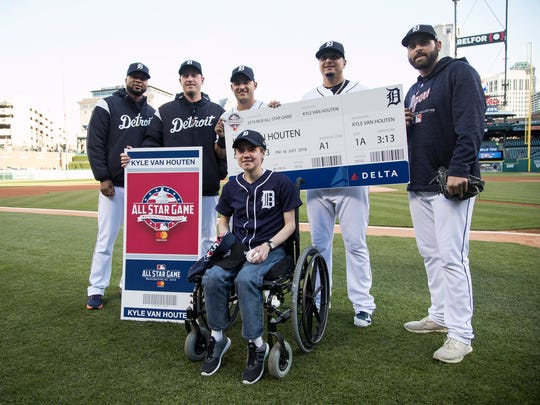 Kyle Van Houten of Hartland, center, who was awarded a trip to this year's All Star Game poses for a photo with Detroit Tigers players on the field before a Detroit Tigers game against Kansas City Royals at Comerica Park in Detroit, Friday, April 20, 2018.