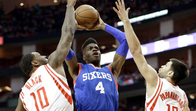 The 76ers' Nerlens Noel is double-teamed by the Houston Rockets' Tarik Black (10) and Kostas Papanikolaou (16) in the first half Friday in Houston.