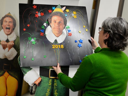 Special events coordinator Mary Yeaple hangs a New Year's 2018 sign on a Buddy the Elf cut out for a social media photo as she and her crew of volunteers work to prepare for New Year's Eve in York City, Tuesday Dec. 26, 2017. John A. Pavoncello photo