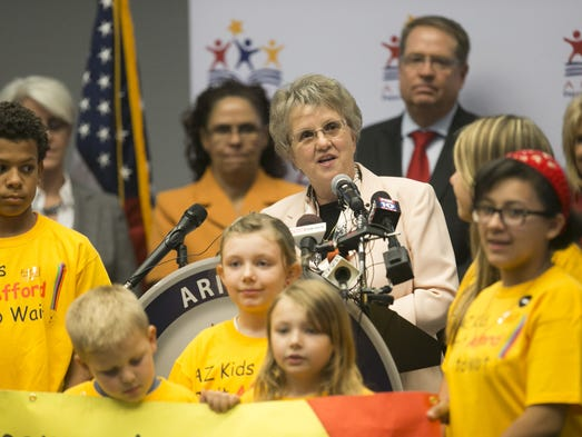 Flanked by children of Arizona Department of Public