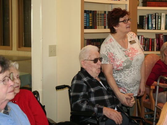 Community relations director Dawn Hull holds the hand of resident Sam Anderson as they listen to Joel Henderson's presentation of the State of Oregon's program Talking Books at Woodland Residential Inn on February 25.