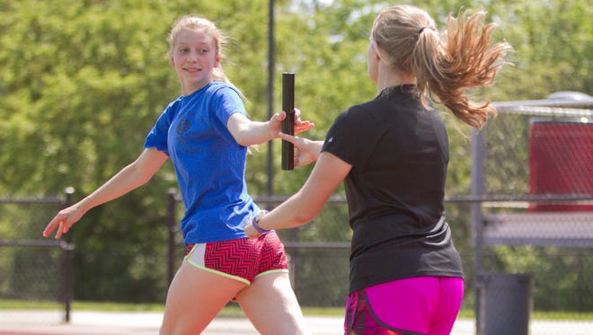 Stellar Student member Abby Hackett receives the baton on the track of Pinckney High School from fellow track member Allie Hartstang. Hackett was a star on the distance runs such as the 4x800m as well as excelling academically.