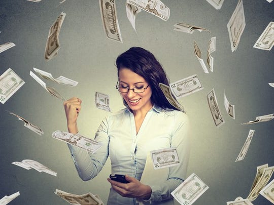 A woman checking her phone and cash money falling around her.