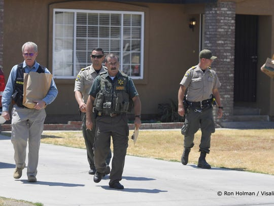 Detectives leave the home of a man who is suspected