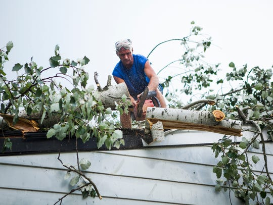 Clarence Robinson Jr. uses a chainsaw to clear large
