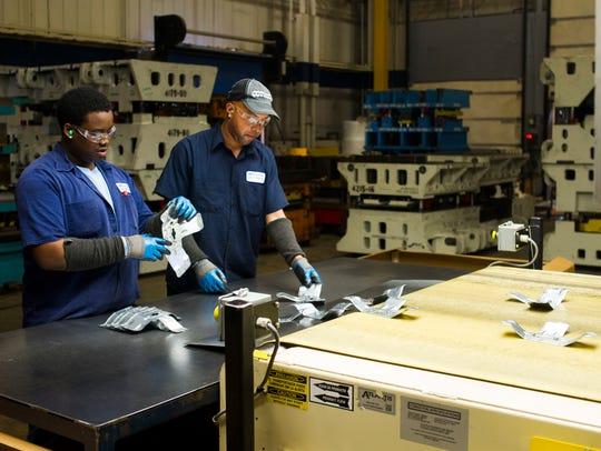 Ben Jackson, left, and Jarret Brown inspect BMW components