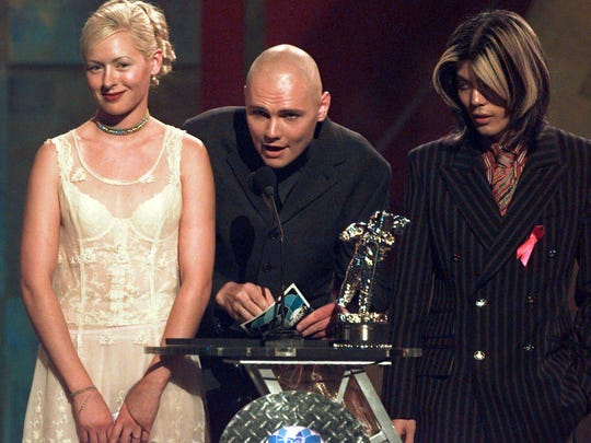 Smashing Pumpkins members D'Arcy Wretzky (from left), Billy Corgan and James Iha appear on stage to accept an award Sept. 4, 1996, at the MTV Video Music Awards in New York.