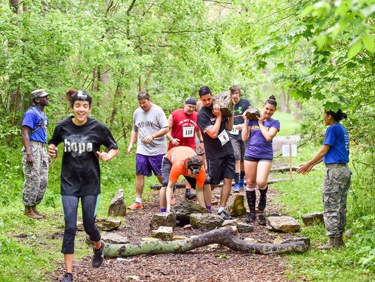 Runners pick up heavy rocks while competing in a obstacle