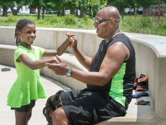 Azyah Walker, 7, and her grandfather Renae 'Pittsburgh' Sparrow, of York, stop to play at the splash pad in Penn Park. The pair were passing by on Sunday and noticed the water feature. The splash pad will officially open June 13.