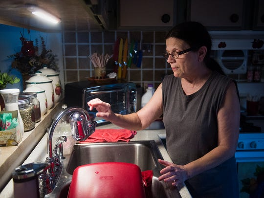 New Oxford Mobile Home Park resident Julie McIntosh uses a water filter attached to her kitchen faucet to help reduce possible elements in her water. 'Water contamination, you think of that as something in Ethiopia, not here in the U.S.,' McIntosh said.