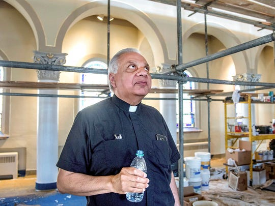 In this June 2, 2017 photo the Rev. Angel Sierra glances up at the scaffolding, which has taken over the sanctuary of the Church of the Forty Martyrs as major renovation work  gets underway in Tuscola, Ill. Two months from now, parishioners at church will be able to establish a cozy new seating arrangement for weekend Mass. The rest of the week, they can relax in their old pews from the comfort of their own homes. To help pay for its $200,000 renovation, and preserve the most cherished parts of the church, Forty Martyrs (est. 1925) sold the pews being replaced for $250 each.