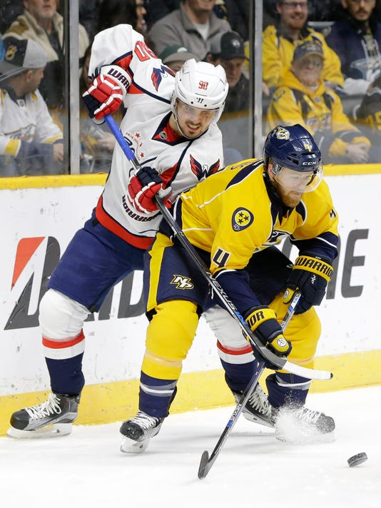 Nashville Predators defenseman Ryan Ellis (4) keeps Washington Capitals forward Marcus Johansson (90), of Sweden, away from the puck in the first period of an NHL hockey game Tuesday, Feb. 9, 2016, in Nashville, Tenn. (AP Photo/Mark Humphrey)