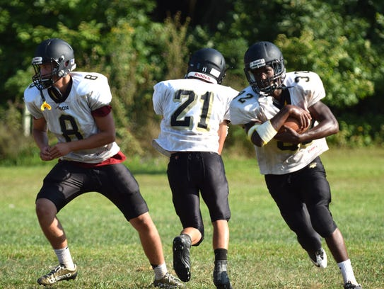 Dylan Thompson, right, heads upfield after taking a