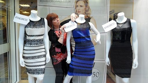 Shop manager Debbie Armstrong adjusts a two tone dress in a window display of a shop in Lichfield, England.. It's the dress that's beating the Internet black and blue. Or should that be gold and white? Friends and co-workers worldwide are debating the true hues of a royal blue dress with black lace that, to many an eye, transforms in one photograph into gold and white.