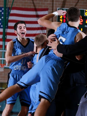 Lansing Catholic players celebrate with fans following their 76-72 win over Williamston Friday, Jan. 27, 2017, in Williamston, Mich.