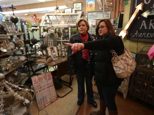 Jennifer Schmit of Ankeny points out an item to her mother, Laurie Ochs, of Moline, Ill., as the two shop at Hinge, an antique and clothing store in Valley Junction, on Small Business Saturday on Saturday, Nov. 29, 2014, in West Des Moines, Iowa.