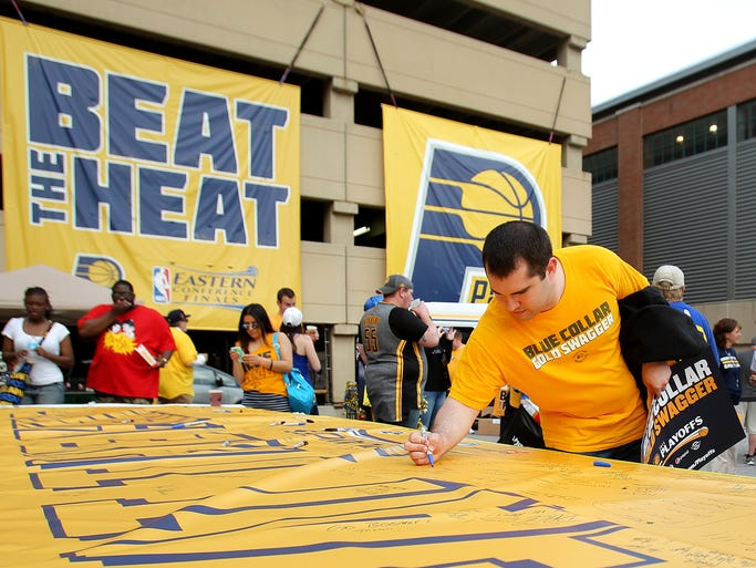 """Mark Bobowsky signs a """"Beat the Heat"""" banner prior to the Indiana Pacers against the Miami Heat during Game 2 of the Eastern Conference Finals at Bankers Life Fieldhouse, Tuesday, May 20, 2014, in Indianapolis."""